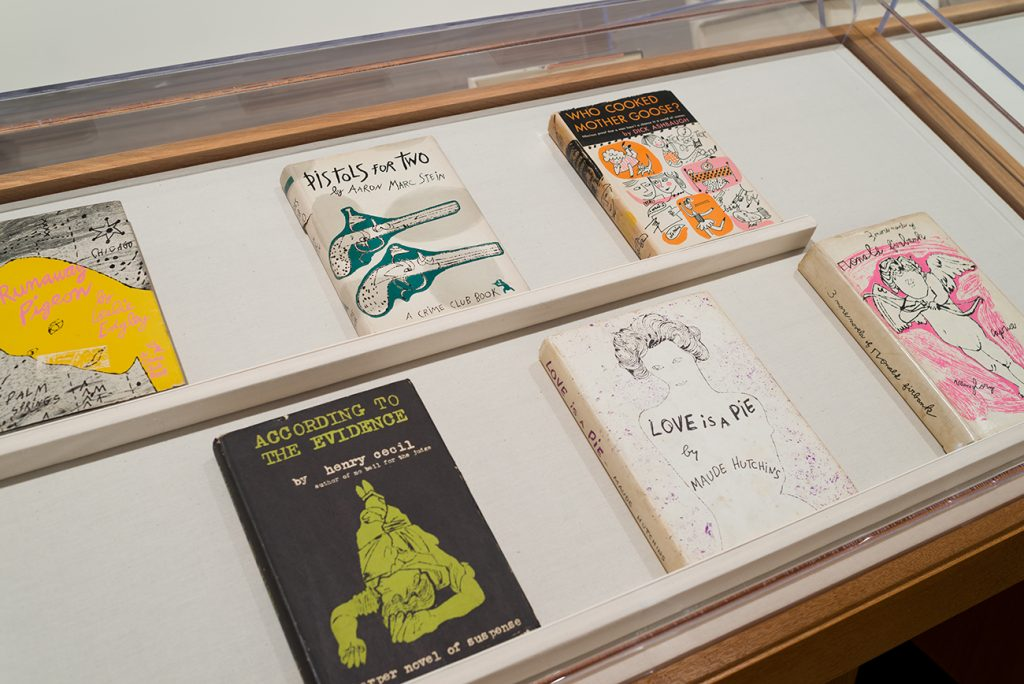 Printed books with various illustrations on their covers in a display case