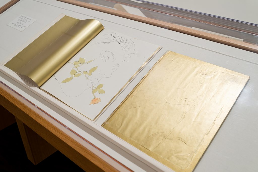 Printed books featuring illustrations using gold leaf embellishments in a display case