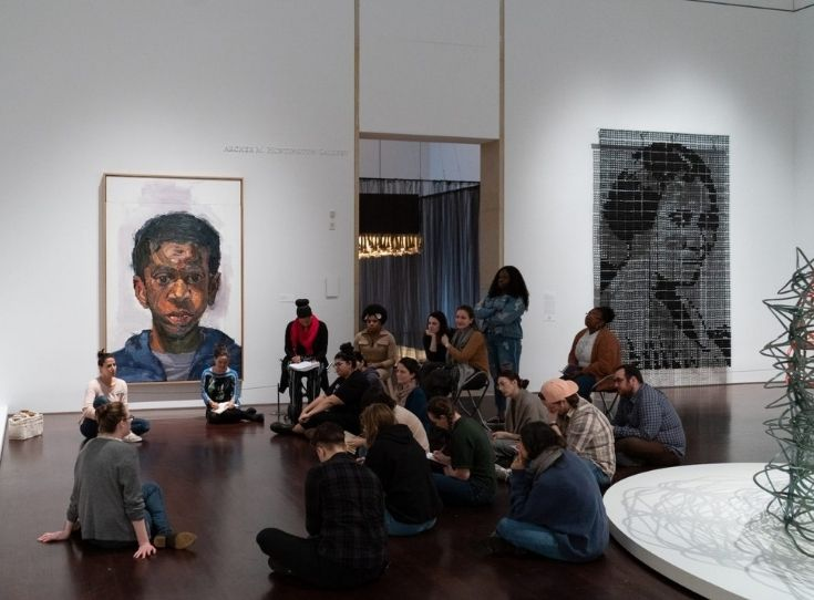 An Education group seated in a semi circle on the floor in the Blanton's Modern/Contemporary gallery