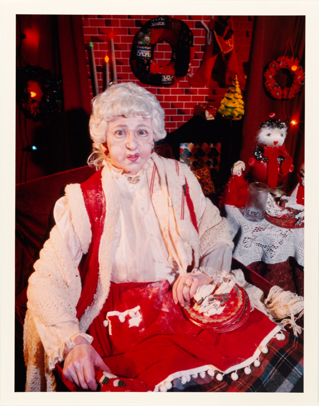 "Photo of a person dressed as ""Mrs Claus"" wearing a white wig and red and white clothing."