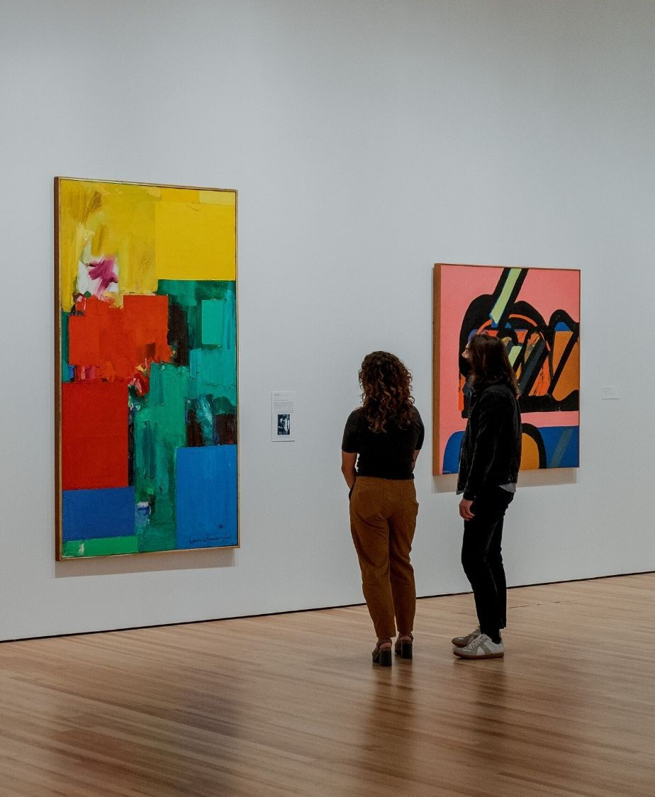 Two people inside a gallery looking at an abstract artwork with prominent yellow, red, green, and blue brushstrokes.