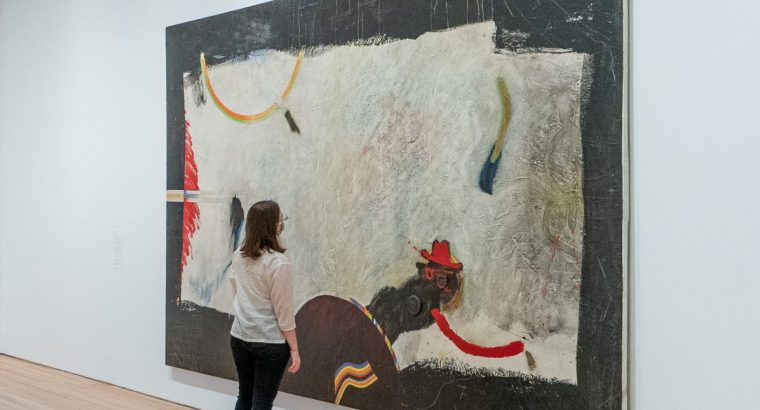 A woman wearing a mask standing in front of a large abstract artwork