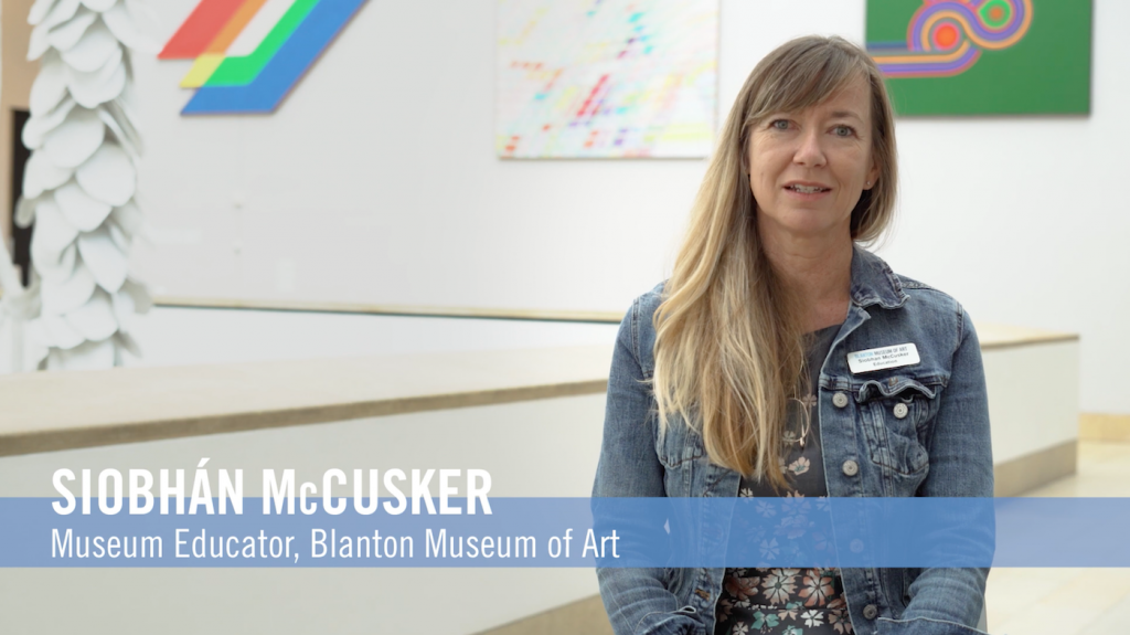 Museum Educator Siobhán McCusker sitting on the mezzanine of the Blanton Museum of Art with artworks behind her on the wall.