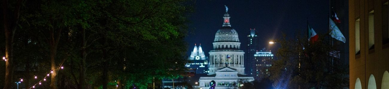 A nighttime photo of the ATX State Capitol taken from the plaza of the Blanton, looking south.