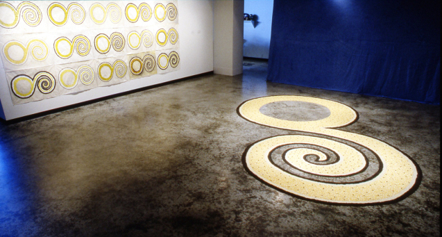 Installation view of artworks, a swirling pattern on the floor, repeated on the wall in a pattern-like presentation.