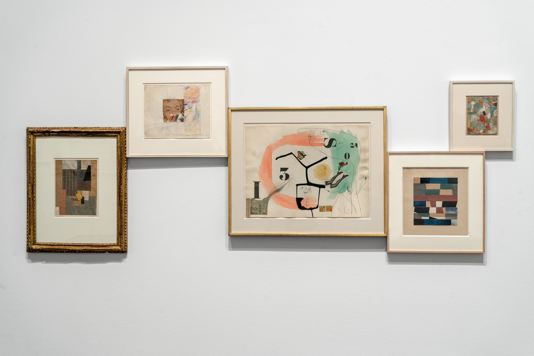 Five framed artworks displayed on a wall.