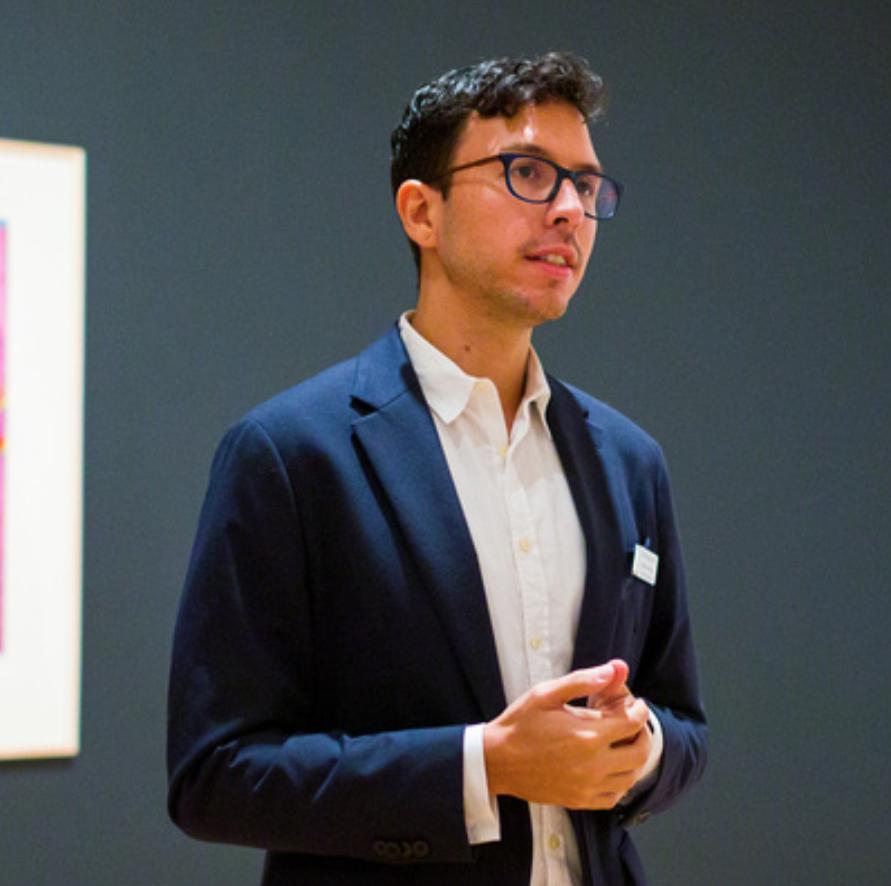 A man wearing a blue jacket wearing glasses, talking in a gallery.